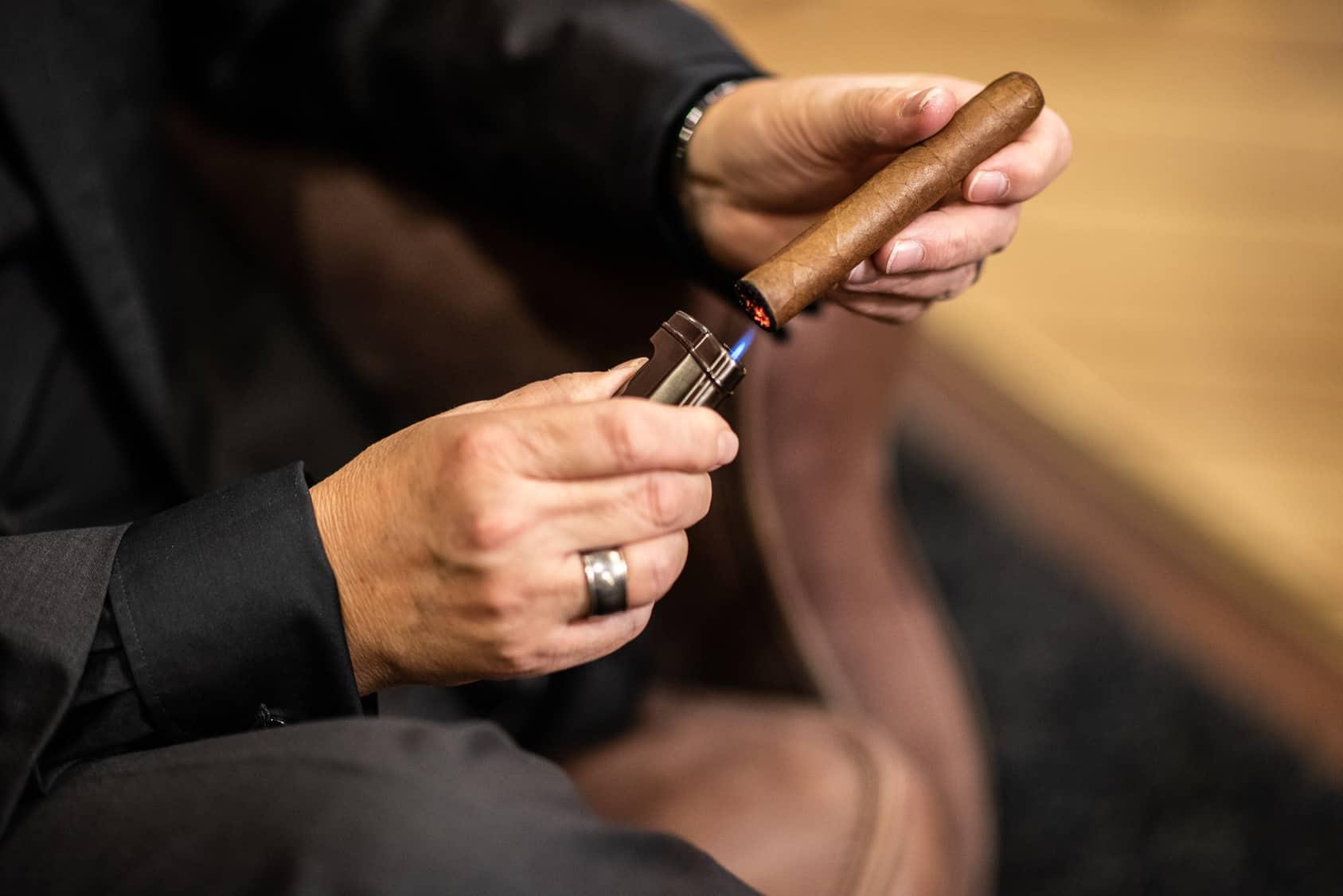 Man in suit lighting a cigar