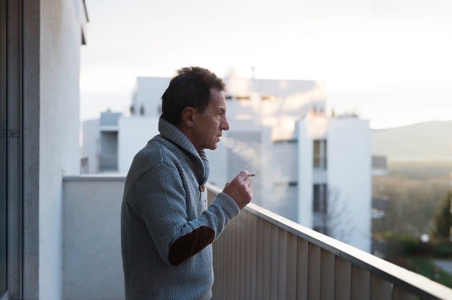 Serious senior man standing on balcony and smoking