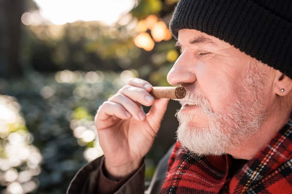 Nice pleasant man smiling while smelling a Cuban cigar