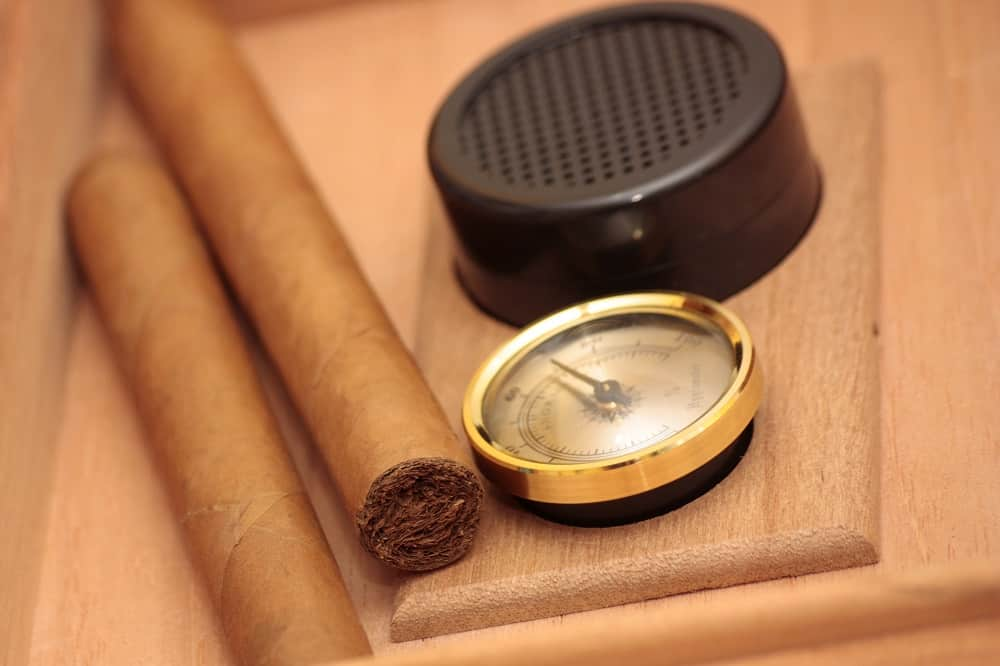 cigars next to a hygrometer