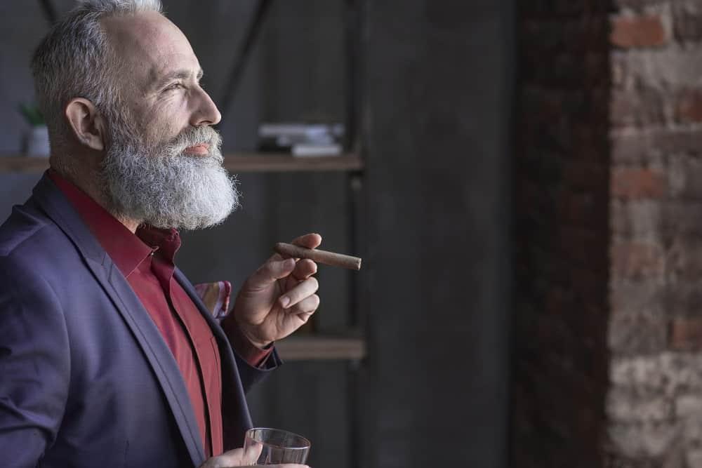 Satisfied senior smoking a cigar